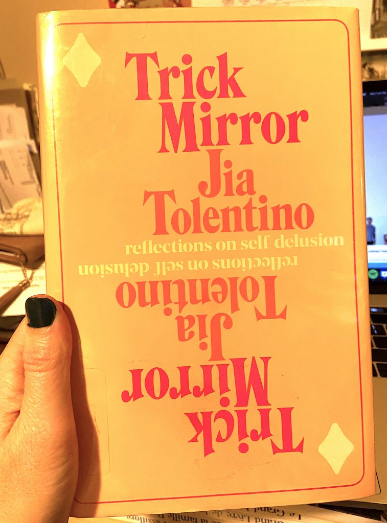 A hand holding a hardcover copy of Trick Mirror by Jia Tolentino.